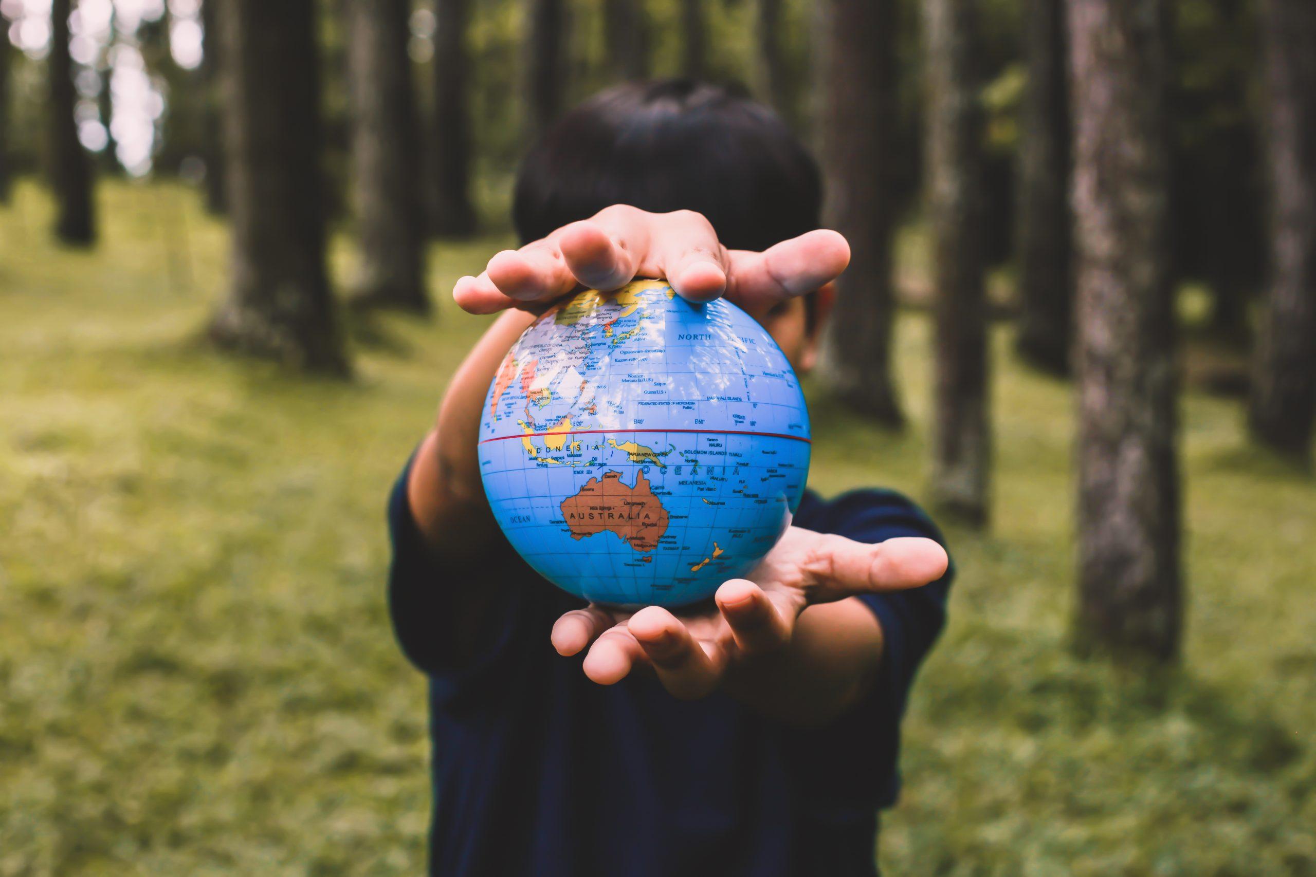 hand holding a globe GVNF6NY